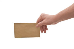 Hand & small envelope. An isolated over white, caucasian man's hand holding a small brown mottled envelope stock photography