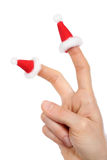 Hand with small Santas caps on fingers Royalty Free Stock Photos