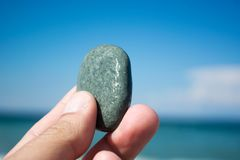 Hand with small stone on the beach Stock Image