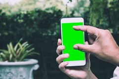 Hand of smart man holding mobile smart phone with chroma green screen and touch to zoom displa Royalty Free Stock Photo