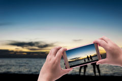 Hand with smart phone shooting photograph Royalty Free Stock Image