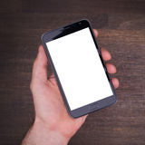 Hand with smart phone on wooden table stock images