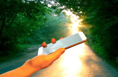 Hand smartphone on the background voshodyaschego sun forest road green forest Stock Images