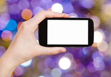 Hand with smartphone on blurred violet background Stock Photos