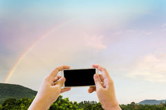 Hand and smartphone or mobile phone taking photo with rainbow. Hand and smartphone or mobile phone taking photo or video clip with rainbow on sky after rain with Royalty Free Stock Photos