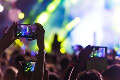 Hand with a smartphone records live music festival. Taking photo of concert stage, live concert, music festival, happy youth, luxury party, landscape exterior Royalty Free Stock Photo