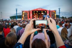 Hand with a smartphone records live music festival, live concert, happy youth Royalty Free Stock Photo