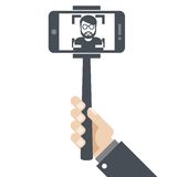 Hand with smartphone on selfie stick Royalty Free Stock Images