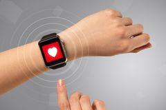 Hand with smartwach and helath concept. Naked female hand with smartwatch and with heart rate icon on the watch Royalty Free Stock Photography