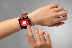 Hand with smartwach and helath concept. Naked female hand with smartwatch and with heart rate icon on the watch Royalty Free Stock Image