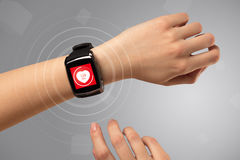 Hand with smartwach and helath concept. Naked female hand with smartwatch and with heart rate icon on the watch Stock Photos