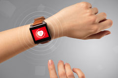 Hand with smartwach and helath concept. Naked female hand with smartwatch and with heart rate icon on the watch Stock Image