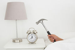Hand smashing alarm clock with hammer in bed Royalty Free Stock Photography