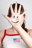 Hand smile. The girl closed the person at hand with the smile symbol on a gray background Stock Photography