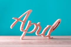 Hand sned träbokstäver som det April ordet 1st dag av det april begreppet Arkivbilder