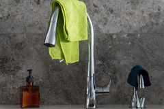 Hand soap pump, chrome kitchen sink faucet, filtered water tap with microfibre cloths, and grey marble stone tile backsplash stock images