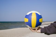 Hand with soccer ball on beach. Hand holding football or soccer ball on sandy beach with sea in background and copy space Stock Photo