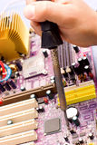 Hand with soldering iron over  motherboard Stock Images