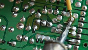 Hand soldering wire onto circuit board stock video footage