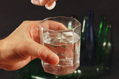 Hand with a soluble tablet from hangover over a glass of water on dark background. Royalty Free Stock Photos