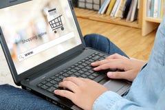Hand som binder bärbar datordatoren med www på sökandestång över suddighetssto Arkivfoto