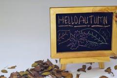 Hand som drar Hellohöst på den svart tavlan Foto för säsongsbetonad lägenhet för höst lekmanna- på träbackgroun arkivbild