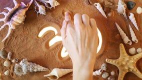 Hand som drar Om-symbol i sanden pink scallop seashell Top beskådar arkivfilmer