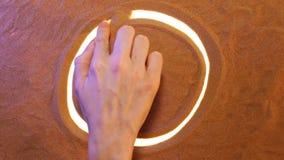 Hand som drar Yin Yang Symbol i sanden pink scallop seashell Top beskådar lager videofilmer