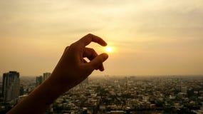 Hand som fångar solnedgången royaltyfria bilder