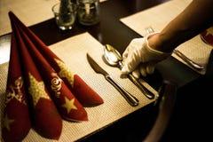 Hand som förlägger disk på dekoren för garneringar för matställe för inställning för tabell för ferie för nytt år för jul Arkivfoton