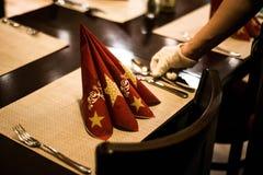 Hand som förlägger disk på dekoren för garneringar för matställe för inställning för tabell för ferie för nytt år för jul Royaltyfri Bild