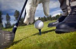 Hand som förlägger en utslagsplats med golfboll Royaltyfria Bilder