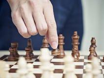 Hand som flyttar ett schackstycke Arkivfoton