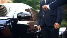 Hand som ger biltangenter till affärsmannen som hyr den lyxiga automatiskn för tur, köp royaltyfria bilder