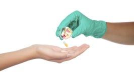Hand som ger kapseln och preventivpilleren Arkivbilder