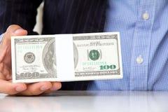 Hand som ger pengar Arkivbild