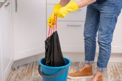 Hand som hemma rymmer en avfallavskrädepåse för att ta den bort arkivfoto