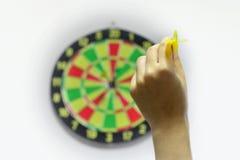 Hand som kastar pilen till darttavlan (som siktar begrepp) Arkivfoto