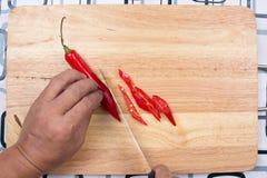 Hand som klipper varma Chili Peppers på träbrett Royaltyfri Foto