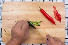 Hand som klipper varma Chili Peppers på träbrett Royaltyfri Bild