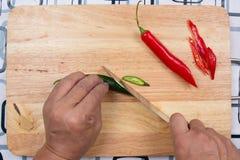 Hand som klipper varma Chili Peppers på träbrett Arkivfoton