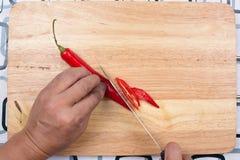 Hand som klipper varma Chili Peppers på träbrett Fotografering för Bildbyråer