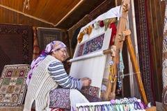 Hand som knyter en orientalisk matta Arkivfoton