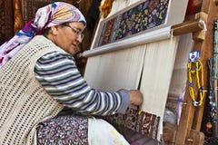 Hand som knyter en orientalisk matta Arkivfoto