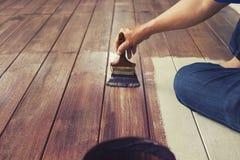 Hand som målar olje- färg på det wood golvet, diy hem- arbetsbegrepp royaltyfri bild