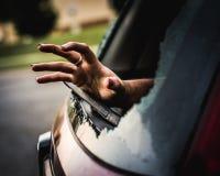 Hand som når till och med ett brutet bilfönster för hjälp royaltyfri fotografi