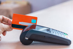 Hand som nallar kreditkorten på pos.-terminalen Royaltyfria Bilder