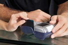 Hand som nallar kreditkorten till och med terminalen på salongen Arkivbild