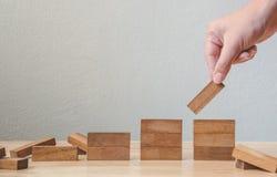 Hand som ordnar träsnittet som staplar som momenttrappan affärsconce Royaltyfri Bild