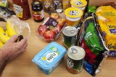 Hand som packar upp livsmedel från en bärkasse Royaltyfria Foton